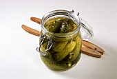 Gherkins in pickling jar, pickle tongs beside it