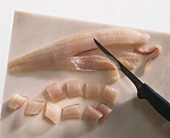 Pike-perch fillet, partly cut into pieces, with knife