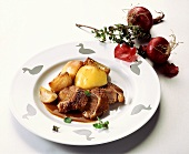 Goose breast with red onions and potatoes on plate