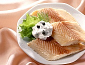 Smoked trout fillets with yoghurt & caper dip on plate