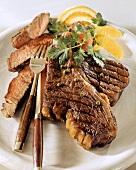 Grilled T-bone steak with green pepper and orange segments