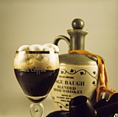Irish coffee in glass, whiskey and two pipes beside it