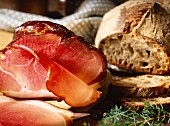 Westphalian ham, cut into and a loaf of rye bread