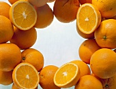 Lots of oranges, whole & halved, grouped round edge of picture