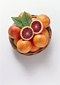 Whole blood oranges & two halves with leaves in basket