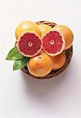 Two pink grapefruit halves on whole grapefruits in basket