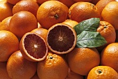 Blood oranges with two blood orange halves and leaves