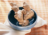 Two ginger roots in a blue bowl