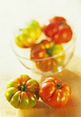 Beefsteak tomatoes, ripe & unripe, in front of & in glass bowl