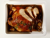 Roast wild boar leg, carved, in glass roasting dish