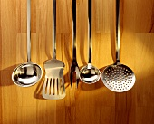 Ladles, spatulas & a meat fork hanging on wooden wall