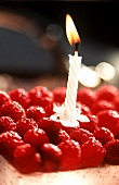 A raspberry slice with a small burning candle