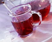 Hot fruit tea (Kaminfeuer) in glass and pot