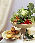 Gemüse in weisser Schale, daneben Kartoffeln auf Teller