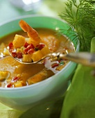 Fish soup with curry in bowl and on spoon