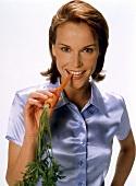 Junge Frau isst eine Möhre