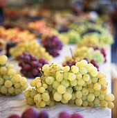 Green and red grapes on marble slab at the market