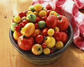 Lots of different tomatoes in wooden dish on wooden platter