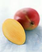 Half a mango beside a whole mango