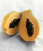 Two papaya halves on light blue background