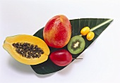 Exotic fruits with drops of water on banana leaf
