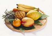 Various exotic fruits with mandarin on wicker plate