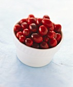 Cranberries in white bowl on pale blue background
