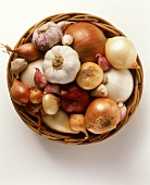 Various types of onion and garlic in a basket