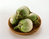 A few green aubergines from Thailand on a wooden plate