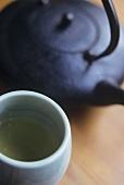 Green Tea in Cup with Tea Pot
