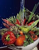 Wasserstrahl trifft auf buntes Gemüse in einer Siebschüssel