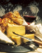 Various types of cheese, bread and glass of red wine