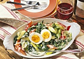 Spinach & leek casserole with medium-soft eggs in oval bowl