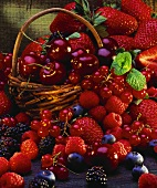 Many different berries and cherries in & around basket
