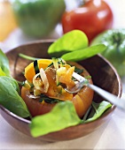 Stuffed tomato with spinach leaves in a wooden bowl