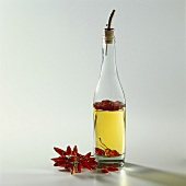 A bottle of chili oil, dried red chilies beside it