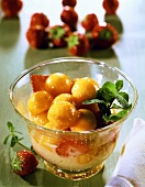 Melon sabayon with strawberries and fresh mint in glass bowl