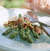 Green asparagus with sausage slices, parmesan, pine nuts
