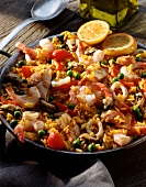 Paella in paella pan on wooden background