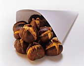 Roasted chestnuts falling out of a paper bag