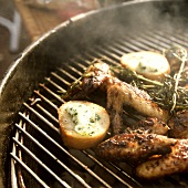 Chicken wings & potatoes on grill rack with sprig of rosemary