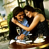 Young couple at café table with olives, champagne, coffee