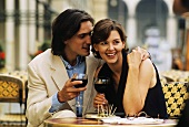 Young couple at café table with red wine