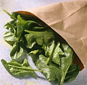 Spinach leaves with drops of water falling out of paper bag