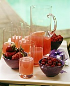 Red berry drink in glasses and a glass jug