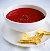 Beetroot soup in a bowl, with taco crisps