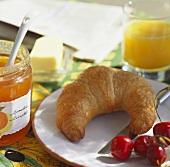 Breakfast scene with croissant, jam, cherries, juice etc