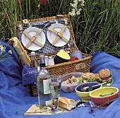 Picknick auf blauer Decke vor offenem Picknickkorb (aussen)