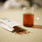 Rooibos tea in tea glass, behind in pack
