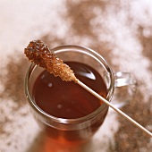 Sugar candy stick on a glass of Rooibos tea